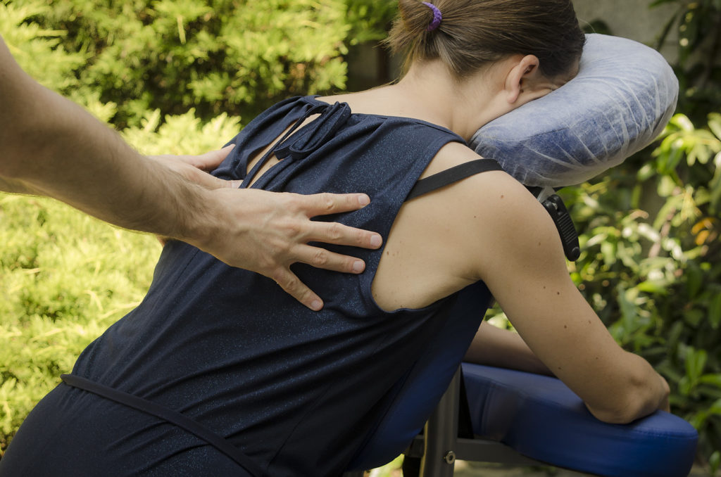 une personne est assise sur une chaise de massage et reçoit un Amma Assis